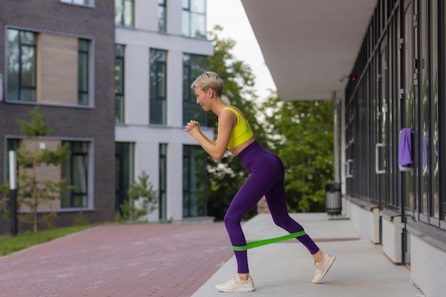 Une jeune sportive avec une bande élastique faisant de l'exercice à l'extérieur en ville.