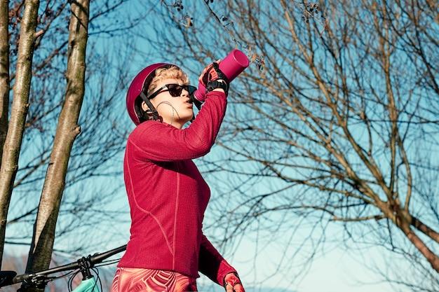 Jeune sportive boit de l'eau de la bouteille de sport