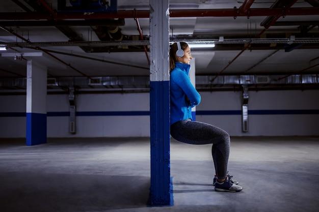 Jeune sportive caucasienne en survêtement en cours d'exécution rapide dans le garage.
