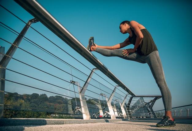 Jeune sportive debout sur le pont avec un pied sur la rampe et se penchant vers elle