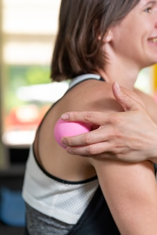 Une jeune sportive fait un massage avec une boule myofasciale. libération myofasciale avec rouleau en mousse. auto-massage.