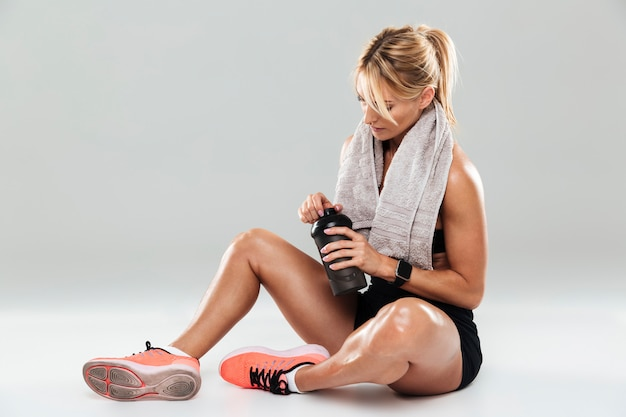 Jeune sportive fatiguée avec une serviette sur ses épaules
