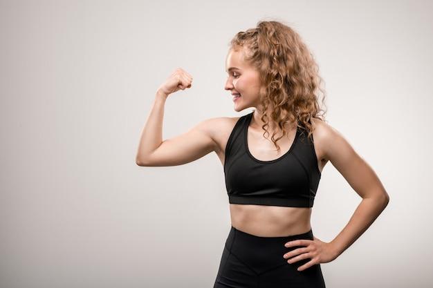 Jeune sportive gaie avec de longs cheveux blonds bouclés en gardant une main sur la taille tout en montrant sa force physique