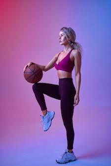 Jeune sportive avec des poses de balle en studio, fond néon. femme de remise en forme à la séance photo, concept sportif, mode de vie actif