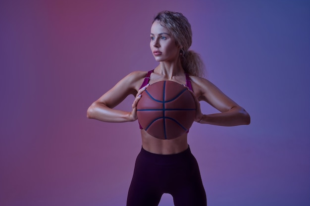 Jeune sportive avec des poses de balle en studio, fond néon