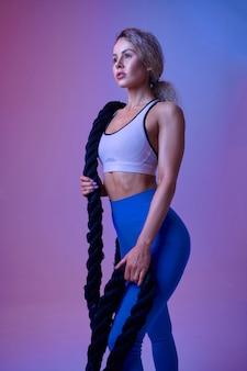 Jeune sportive avec des poses de cordes en studio. femme de remise en forme à la séance photo, concept sportif, mode de vie actif