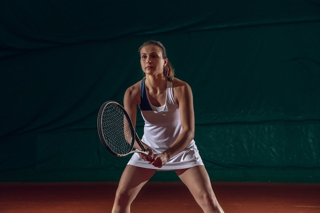 Jeune sportive professionnelle caucasienne jouant au tennis sur le mur du terrain de sport. entraînement, pratique en mouvement, action. puissance et énergie. mouvement, publicité, sport, concept de mode de vie sain. vue de face.