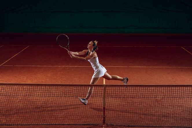 Jeune sportive professionnelle caucasienne jouant au tennis sur un terrain de sport. entraînement, pratique en mouvement, action. puissance et énergie. mouvement, publicité, sport, concept de mode de vie sain. angle élevé.