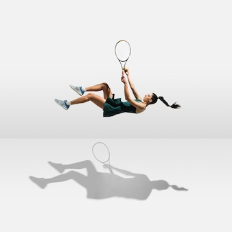 Jeune sportive professionnelle en lévitation volant tout en jouant au tennis isolé sur mur blanc