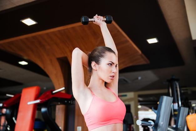 Jeune sportive séduisante sérieuse faisant des exercices de remise en forme pour les muscles des bras à l'aide d'haltères en salle de sport