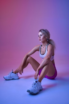 Jeune sportive sexy assise sur le sol en studio, fond néon. femme de remise en forme à la séance photo, concept sportif, motivation de style de vie actif