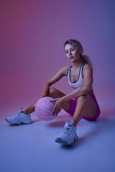 Jeune sportive sexy avec ballon assis sur le sol en studio, fond néon