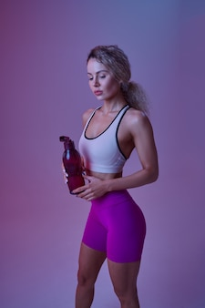 Jeune sportive sexy boit de l'eau en studio, fond néon