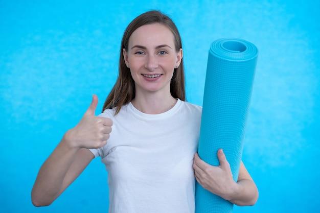 Jeune sportive tenant un tapis de fitness en position debout