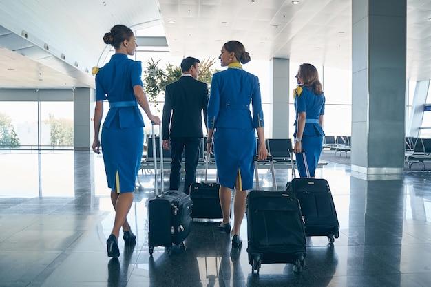 Jeune steward caucasien aux cheveux noirs et ses collègues féminines tirant leurs bagages