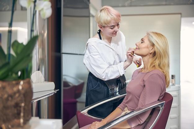 Jeune styliste attentive gardant le sourire sur son visage tout en travaillant avec son client