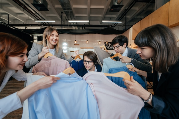 Jeune styliste regardant à travers un ensemble de chemises pour le tournage de mode