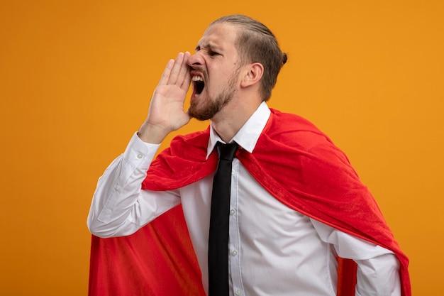 Jeune super-héros guy debout en vue de profil portant une cravate appelant quelqu'un isolé sur fond orange