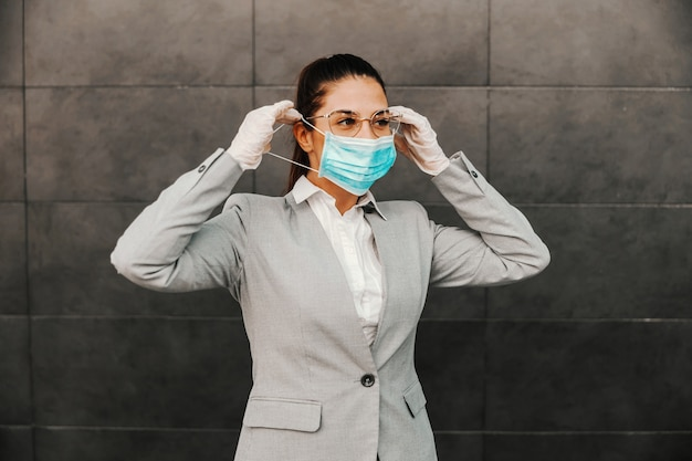 Jeune superbe brune habillée chic et décontractée debout à l'extérieur et mettant un masque facial pendant l'épidémie de virus covid.