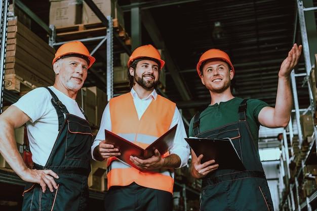 Jeune superviseur en conversation avec des ouvriers d'entrepôt