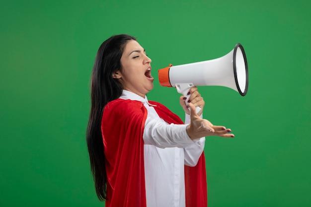 Jeune superwoman debout en vue de profil parler dans le haut-parleur à la main qui s'étend tout droit isolé sur le mur vert