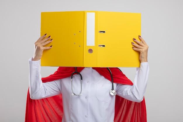 Jeune superwoman portant un stéthoscope tenant le presse-papiers devant son visage se cachant derrière isolé sur mur blanc