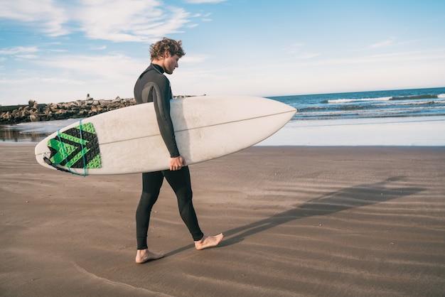 Jeune surfeur debout dans l'océan avec sa planche de surf dans un costume de surf noir. concept de sport et de sports nautiques.