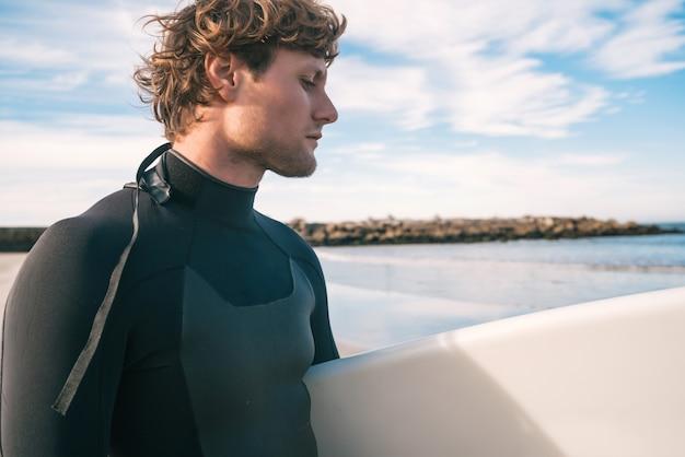 Jeune surfeur debout dans l'océan avec sa planche de surf dans un costume de surf noir