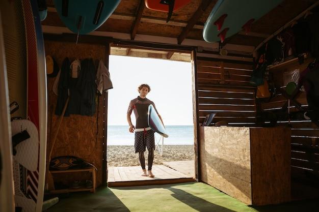 Jeune surfeur guy transportant une planche de surf à la cabane de surf à la plage