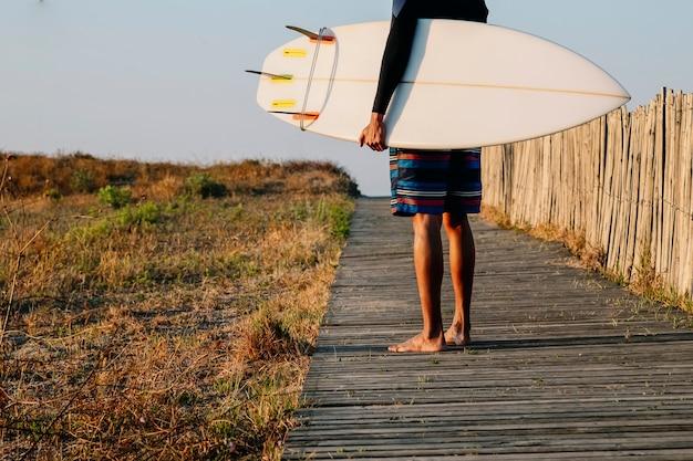 Un jeune surfeur méconnaissable tient une planche de surf à l'aube d'un sport extrême