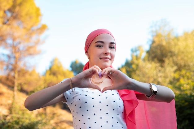 Jeune survivante du cancer du sein, main dans la main symbole du coeur