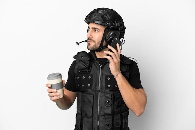 Jeune swat caucasien isolé sur fond blanc tenant du café à emporter et un mobile
