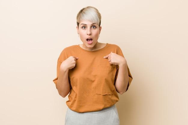 Jeune taille plus femme aux cheveux courts surpris en pointant avec le doigt, souriant largement.