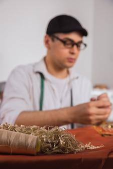 Jeune tailleur masculin travaillant dans son atelier.