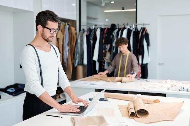 Jeune tailleur en tenue décontractée debout par 24 devant un ordinateur portable tout en surfant sur le net pour les nouveaux modèles de mode