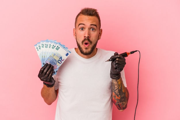 Jeune tatoueur caucasien tenant des factures isolées sur fond rose