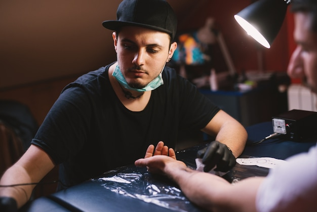 Le jeune tatoueur professionnel choisit soigneusement le stylo de tatouage à utiliser pour le tatouage du bras de son client.