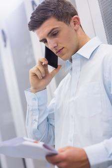 Jeune technicien appelant et lisant un document