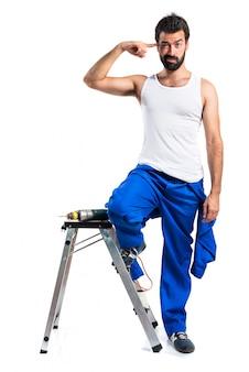 Jeune technicien électrique avec un foret faisant un geste fou