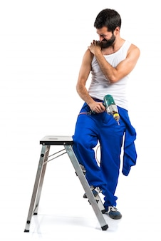 Jeune technicien électrique avec une perceuse avec douleur à l'épaule