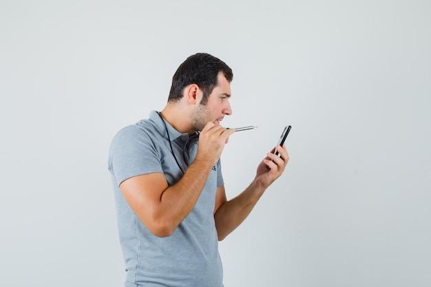 Jeune technicien essayant d'ouvrir le dos de son smartphone en utilisant une perceuse en uniforme gris et en regardant concentré.