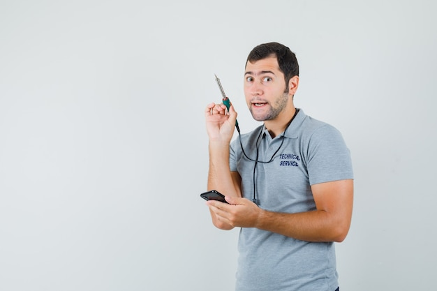 Jeune technicien essayant d'ouvrir son smartphone en utilisant une perceuse en uniforme gris et en regardant concentré.
