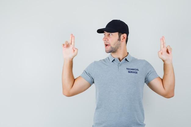 Jeune technicien faisant signe de pistolet à doigt en uniforme gris et à la confiance.