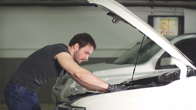 Jeune technicien homme faisant service moteur de voiture dans le garage.