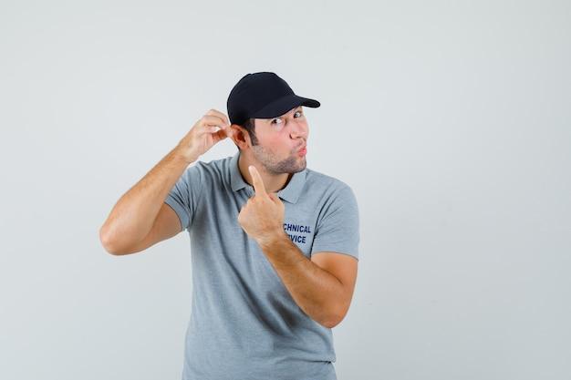 Jeune technicien pointant son oreille en uniforme gris.