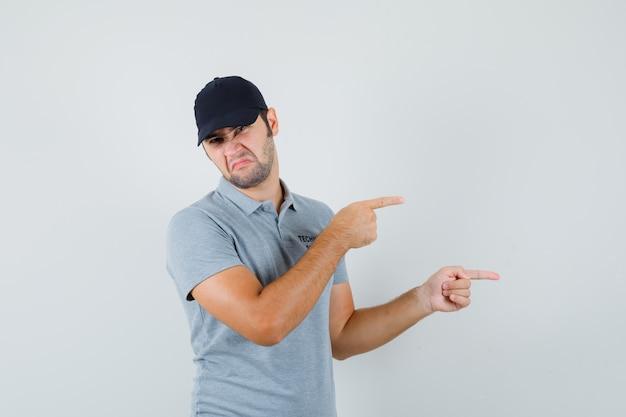 Jeune technicien pointant vers le côté droit en uniforme gris et l'air désespéré.