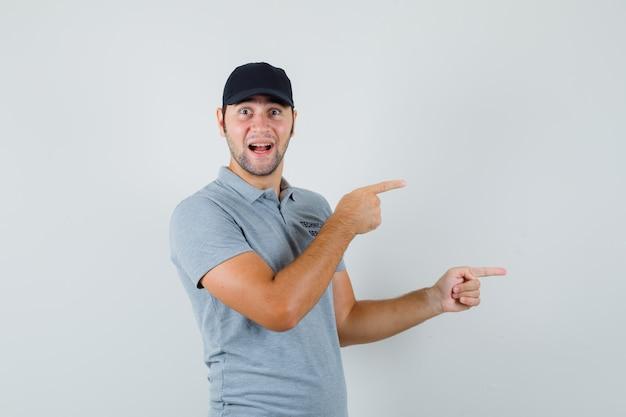 Jeune technicien pointant vers le côté droit en uniforme gris et l'air joyeux.