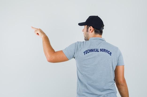 Jeune technicien pointant vers l'extérieur en uniforme et regardant focalisé, vue arrière.