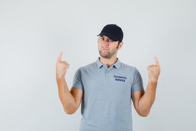 Jeune technicien pointant vers le haut en uniforme gris et l'air hésitant.