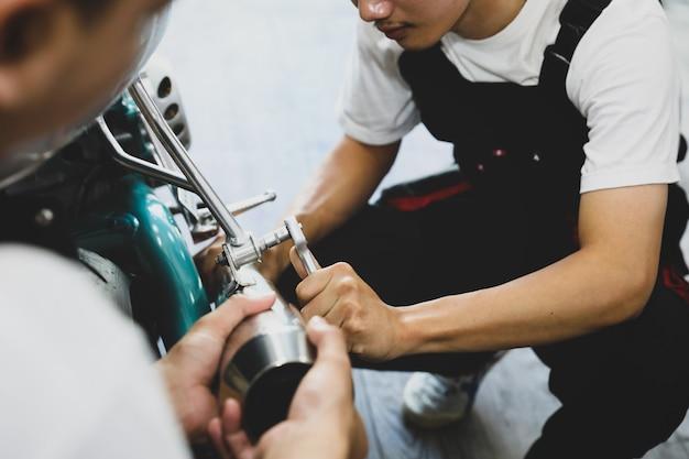 Jeune technicien professionnel d'entretien moto avec équipe au magasin de service.